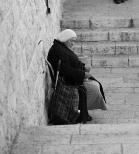 Black and White Image of a widow sitting next to a wall